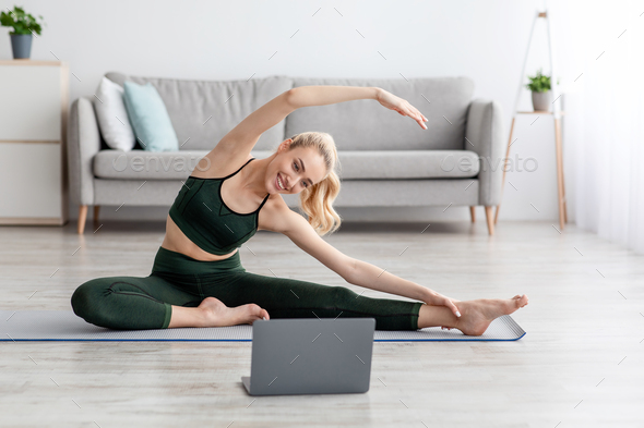 Active woman doing stretching exercise in living room at home - Stock Photo - Images