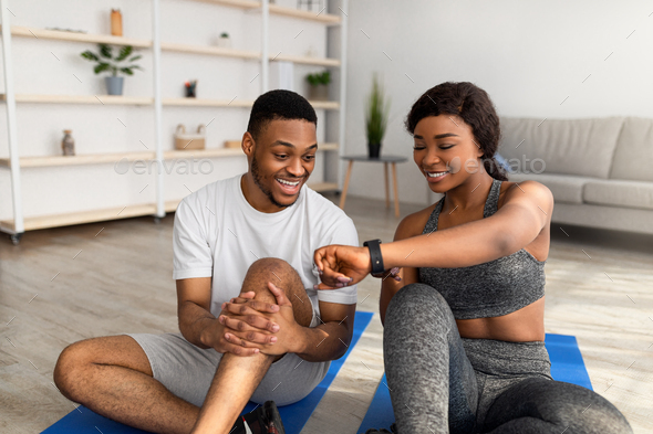 Sporty black lady showing data on smartwatch or fitness tracker to her boyfriend after home workout - Stock Photo - Images