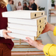 Young smiling blond female in smart casualwear taking stack of packed pizza - PhotoDune Item for Sale