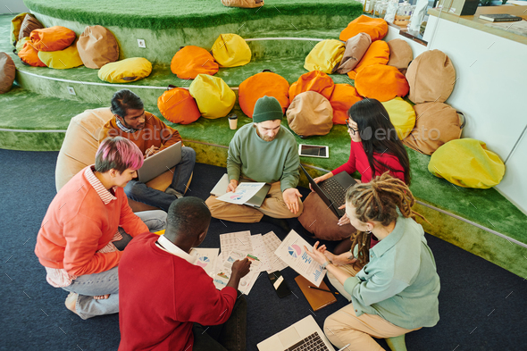 Group of young intercultural financial managers in casualwear discussing papers - Stock Photo - Images