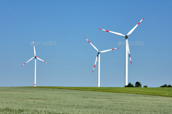 Wind turbines in a grainfield with flying birds - Stock Photo - Images