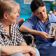 Social worker holding smartphone for disabled senior retired woman during video call - PhotoDune Item for Sale