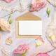 Pink flowers and a blank card with envelope laying on a marble table - PhotoDune Item for Sale