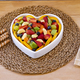Fresh fruit salad in a heart shape plate. Wooden rustic table, biscuits. Healthy eating - PhotoDune Item for Sale