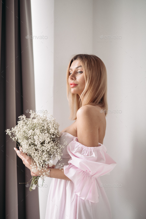 Pretty smiling young woman standing with a bouquet of flowers - Stock Photo - Images