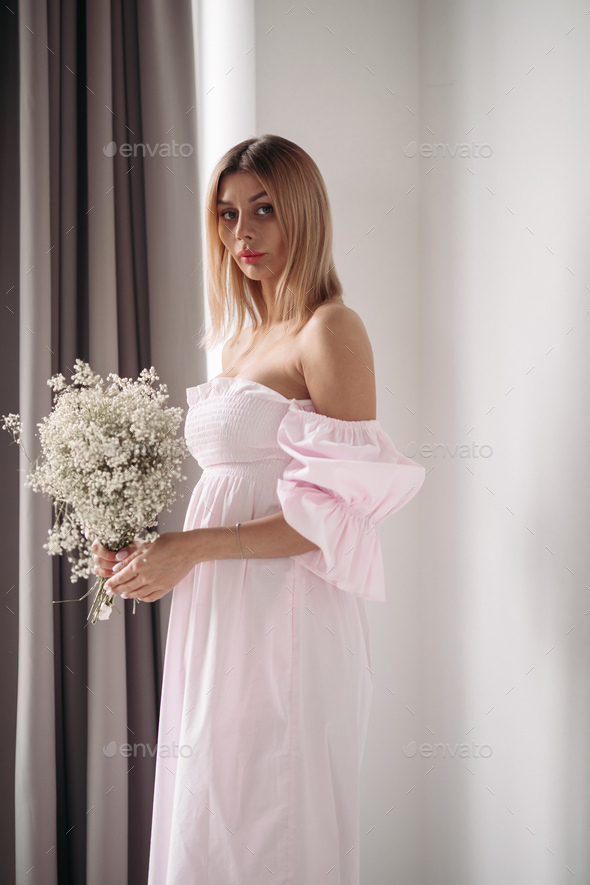 beautiful young girl in white dress holding a boquet of white flowers - Stock Photo - Images