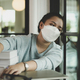 A Female asian student wearing a medical mask sits by the window looking out. - PhotoDune Item for Sale