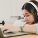 Asian female student sleeping while studying online with laptop and headphones. - PhotoDune Item for Sale