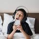 Asian boy singing while listening music on headphone - PhotoDune Item for Sale