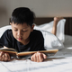 Asian boy reading a book on bed - PhotoDune Item for Sale