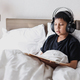 Boy with headphone and reading a book on the bed - PhotoDune Item for Sale