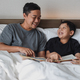 Asian father and son reading a story book before sleep - PhotoDune Item for Sale