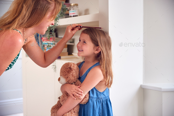 Mother Measuring Daughter's Height And Marking On Wall At Home - Stock Photo - Images