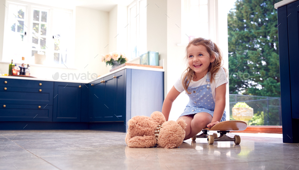 Smiling Young Girl Playing Game Sitting On Skateboard With Teddy Bear At Home - Stock Photo - Images
