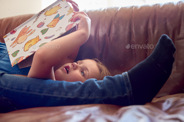 Close Up Of Father And Daughter Lying On Sofa At Home As Girl Reads Book - Stock Photo - Images