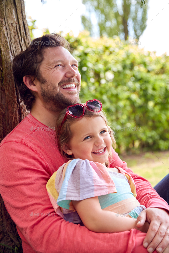 Loving Father Cuddling Young Daughter Sitting Under Tree In Garden Together - Stock Photo - Images