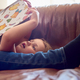 Close Up Of Father And Daughter Lying On Sofa At Home As Girl Reads Book - PhotoDune Item for Sale