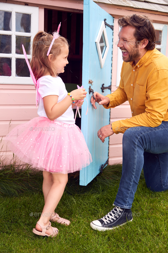 Father With Daughter Wearing Fairy Costume Playing Outdoors In Garden By Playhouse - Stock Photo - Images