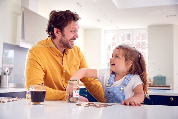 Father And Daughter Counting Pocket Money In Jar On Kitchen Counter - Stock Photo - Images