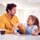 Father And Daughter Counting Pocket Money In Jar On Kitchen Counter - PhotoDune Item for Sale