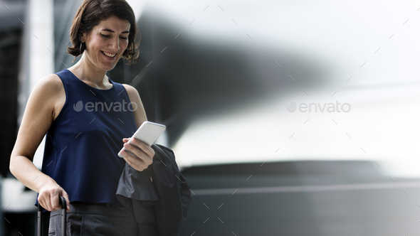 Smiling businesswoman using her phone - Stock Photo - Images