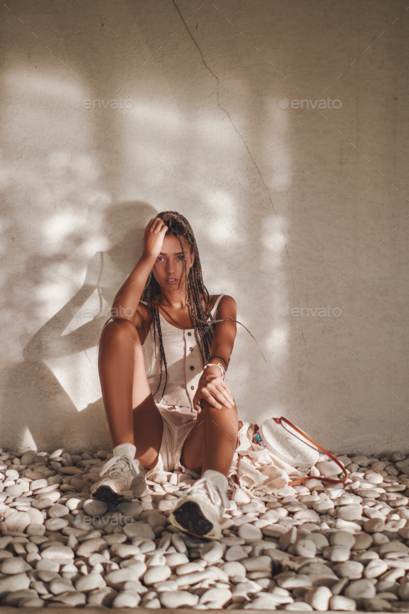 Tanned woman with dreadlocks sitting around wall - Stock Photo - Images
