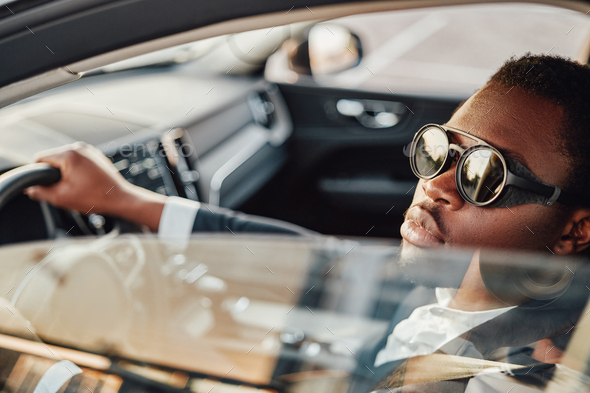 Serious african american businessman inside of car - Stock Photo - Images