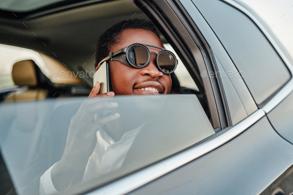 Happy african businessman with phone inside of car - Stock Photo - Images