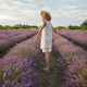 Dreamy teenager girl in straw hat walks in lavender field. Beauty of nature, summer lifestyle - PhotoDune Item for Sale