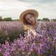 Dreamy teenager girl in straw hat sits in lavender field. Beauty of nature, summer lifestyle - PhotoDune Item for Sale