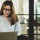Asian woman in glasses looking down at laptop, she is working in a coffee shop, front view shot. - PhotoDune Item for Sale