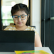 Asian girl wearing glasses looking at tablet to study online. - PhotoDune Item for Sale