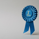 Blue rosette first place on a gray background as a reward for achievement, success and victory. - PhotoDune Item for Sale