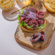 Hamburger with sliced pastrami served with lettuce on a freshly baked sesame bun over white - PhotoDune Item for Sale