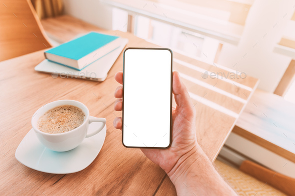 Blank mobile smart phone screen mock up. Man holding smartphone over desk with coffee cup at home. - Stock Photo - Images