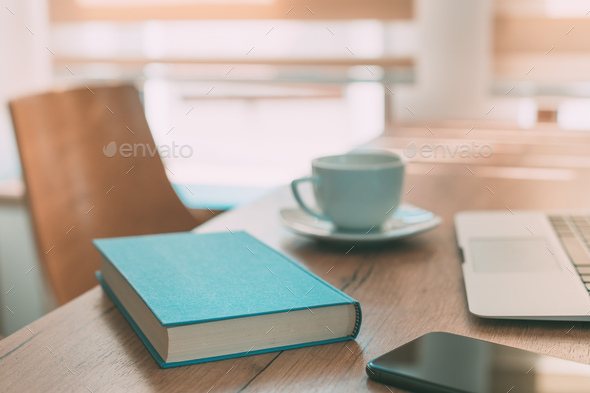Working from home office, living room desk as workspace with book, laptop, smartphone and coffee cup - Stock Photo - Images