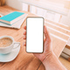 Blank mobile smart phone screen mock up. Man holding smartphone over desk with coffee cup at home. - PhotoDune Item for Sale