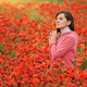 Cute young woman in big meadow of poppies. - PhotoDune Item for Sale