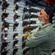 Man choosing pistol at the showcase in gun store - PhotoDune Item for Sale