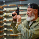 Bearded man twitches the pistol bolt in gun store - PhotoDune Item for Sale