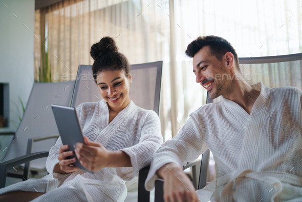 Portrait of young couple relaxing in spa resort, using tablet - Stock Photo - Images