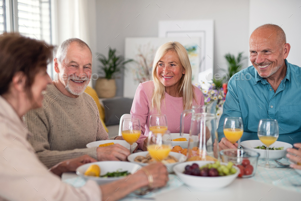 Group of senior friends having party indoors, talking when eating at the table - Stock Photo - Images