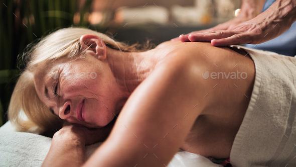 Senior woman having back massage at the spa - Stock Photo - Images