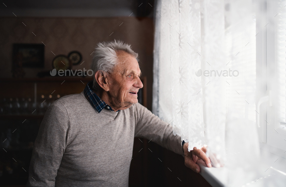Portrait of elderly man standing indoors at home, looking out through window - Stock Photo - Images