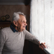 Portrait of elderly man standing indoors at home, looking out through window - PhotoDune Item for Sale