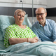 Retired hospitalized sick woman lying in bed with husband visitor sitting beside her - PhotoDune Item for Sale