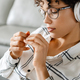 Young curly woman in headphones using laptop while sitting on armchair - PhotoDune Item for Sale