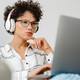 Young curly woman in headphones using laptop while sitting on couch - PhotoDune Item for Sale