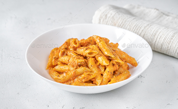 Portion of penne pasta with orange pesto sauce - Stock Photo - Images