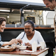 Multiracial women eating at food truck restaurant outdoor - Focus on african woman face - PhotoDune Item for Sale